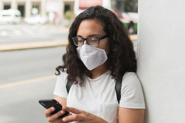 Jonge vrouw die een medisch masker draagt terwijl het controleren van haar telefoon