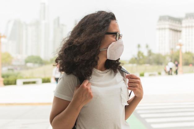 Jonge vrouw die een medisch masker draagt terwijl weg het kijken