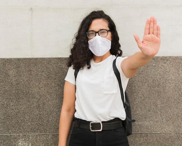 Jonge vrouw die een medisch masker in openlucht draagt
