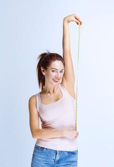 Jonge vrouw die een meetlint vasthoudt en haar lichaamsdelen meet