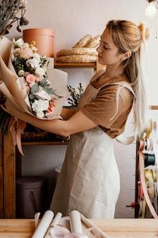 Jonge vrouw die een mooie bloemenregeling maakt