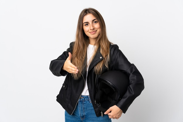 Jonge vrouw die een motorfietshelm over geïsoleerd wit muurhandenschudden houden na veel