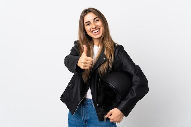 Jonge vrouw die een motorfietshelm over geïsoleerde witte muur houdt die duimen op gebaar geeft