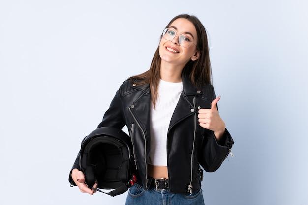 Jonge vrouw die een motorfietshelm over het geïsoleerde blauwe muur geven houden duimen op gebaar