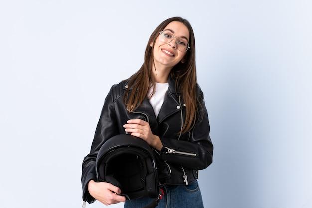 Jonge vrouw die een motorfietshelm over het geïsoleerde blauwe muur toejuichen houdt