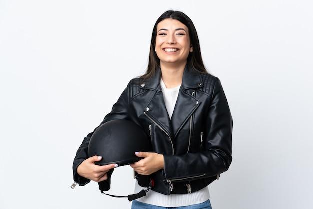 Jonge vrouw die een motorfietshelm over het geïsoleerde witte toejuichen houdt