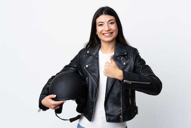 Jonge vrouw die een motorfietshelm over het witte muur geven houden duimen omhoog gebaar