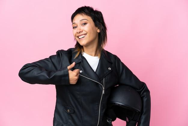 Jonge vrouw die een motorfietshelm over roze muur geven die duimen op gebaar houdt