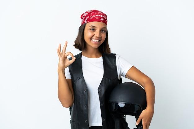 Jonge vrouw die een motorhelm houdt die op wit wordt geïsoleerd dat ok teken met vingers toont
