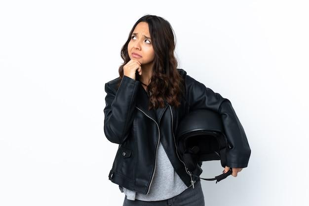 Jonge vrouw die een motorhelm houdt over geïsoleerde witte muur die twijfels heeft en met verwarde gezichtsuitdrukking