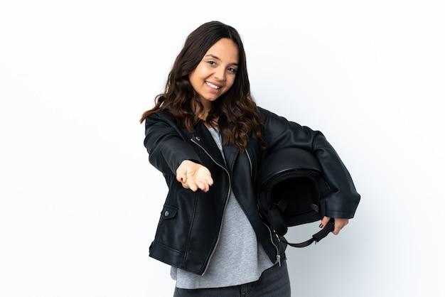 Jonge vrouw die een motorhelm over geïsoleerde witte achtergrond houdt die copyspace denkbeeldig op de palm houdt om een advertentie in te voegen