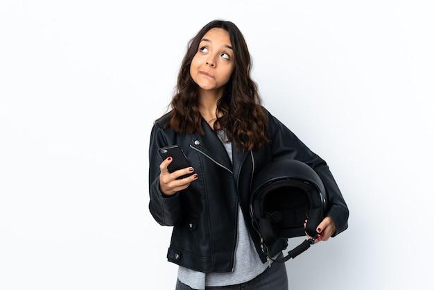 Jonge vrouw die een motorhelm over geïsoleerde witte houdt die koffie houdt om mee te nemen en een mobiel terwijl hij iets denkt