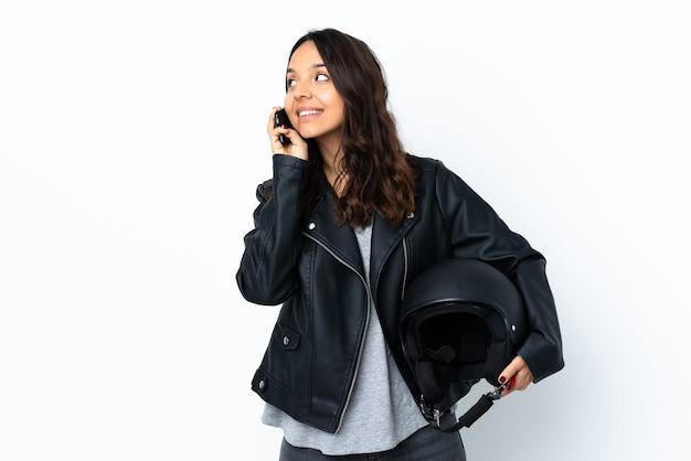Jonge vrouw die een motorhelm over geïsoleerde witte muur houdt die een gesprek met de mobiele telefoon met iemand houdt