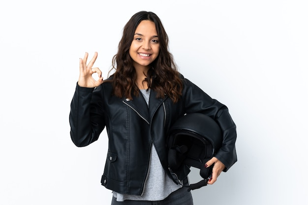 Jonge vrouw die een motorhelm over geïsoleerde witte muur houdt die ok teken met vingers toont