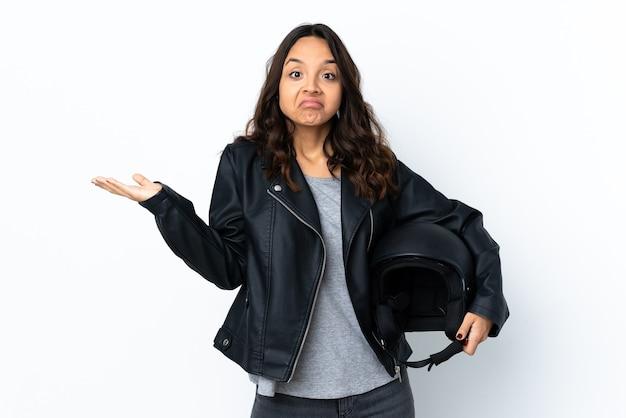 Jonge vrouw die een motorhelm over geïsoleerde witte muur houdt die twijfels heeft terwijl het opheffen van handen