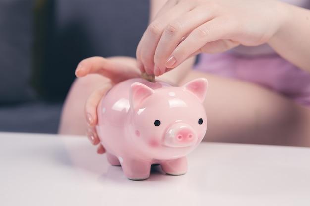 Jonge vrouw die een muntstuk binnen spaarvarken zet als besparingen voor investering