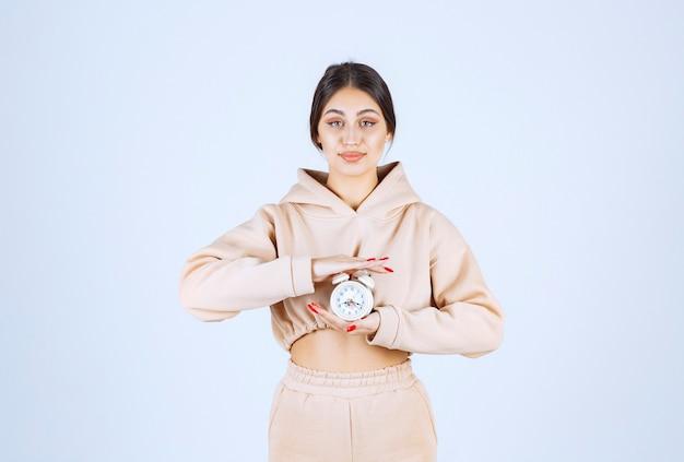 Jonge vrouw die een nieuw model van wekker houdt en bevordert