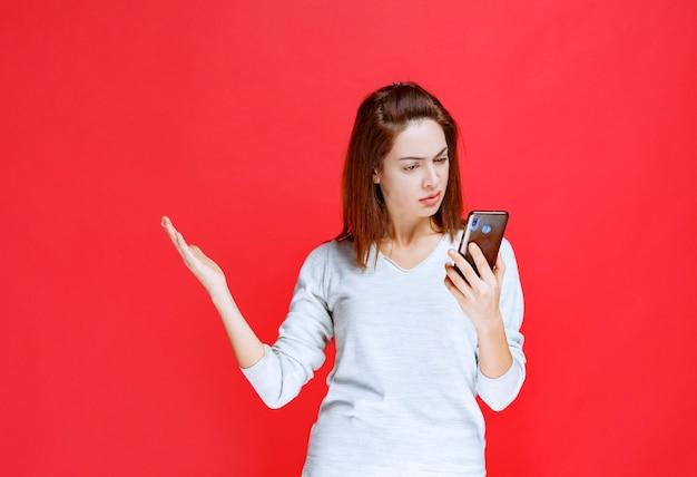 Jonge vrouw die een nieuw model zwarte smartphone vasthoudt en een videogesprek voert of haar selfie neemt
