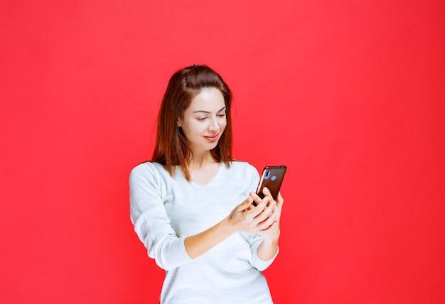 Jonge vrouw die een nieuw model zwarte smartphone vasthoudt en iets sms't of plaatst