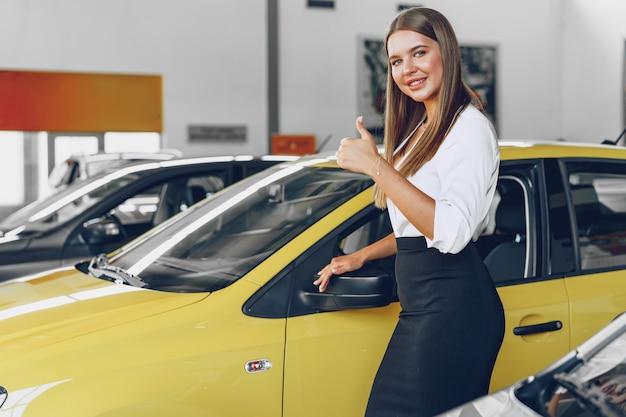 Jonge vrouw die een nieuwe auto controleert die zij gaat kopen