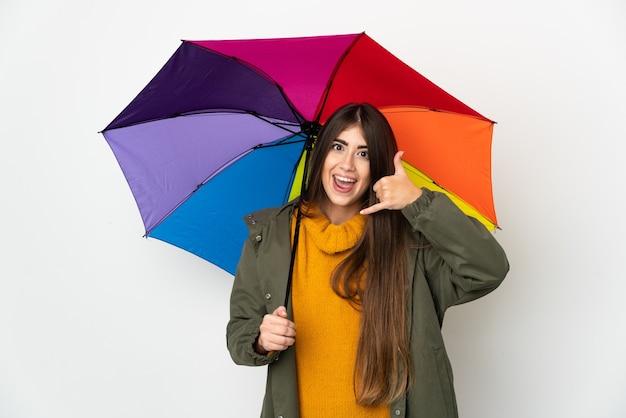 Jonge vrouw die een paraplu houdt die op witte muur wordt geïsoleerd die telefoongebaar maakt. bel me terug teken