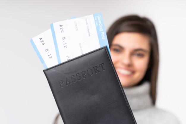 Jonge vrouw die een paspoort over muur houdt