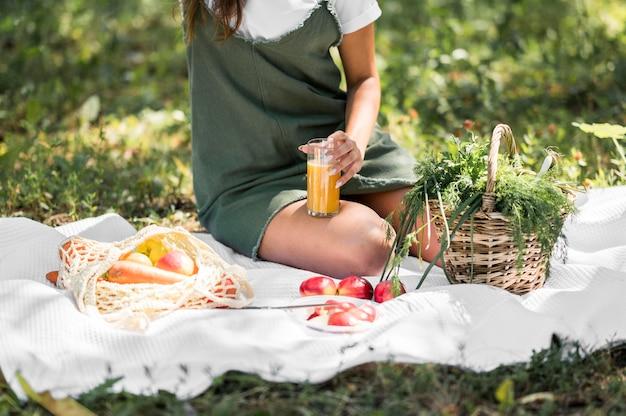 Jonge vrouw die een picknick met gezonde snacks heeft