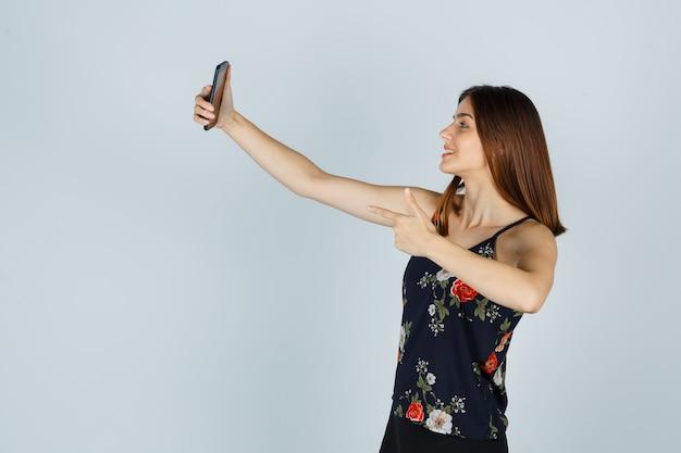 Jonge vrouw die een pistoolgebaar toont terwijl ze selfie op smartphone in blouse neemt en er zelfverzekerd uitziet, vooraanzicht.