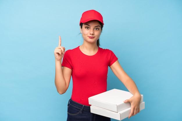Jonge vrouw die een pizza over geïsoleerde roze muur houdt die met de wijsvinger een groot idee richt