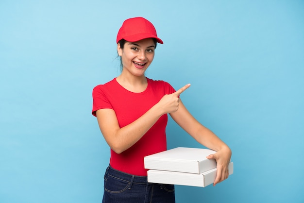 Jonge vrouw die een pizza over geïsoleerde roze muur houdt die vinger aan de kant richt