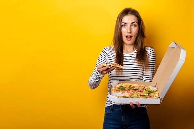 Jonge vrouw die een plak van hete verse pizza met verpakking op geel eet.