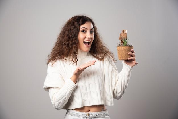 Jonge vrouw die een plant vasthoudt en erop richt. hoge kwaliteit foto