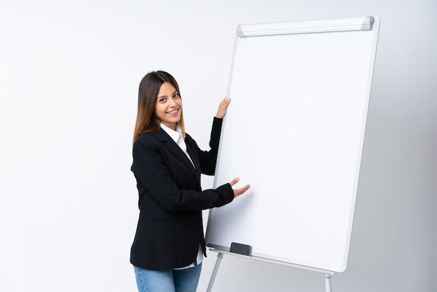 Jonge vrouw die een presentatie op wit bord geeft