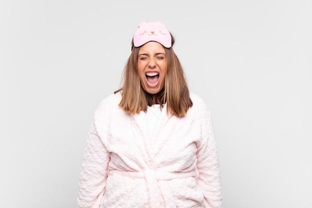 Jonge vrouw die een pyjama draagt, agressief schreeuwt, erg boos, gefrustreerd, verontwaardigd of geïrriteerd kijkt, nee schreeuwt