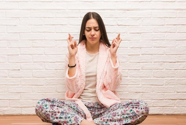 Jonge vrouw die een pyjama draagt die de vingers kruist om geluk te hebben