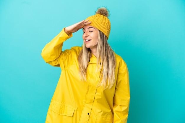 Jonge vrouw die een regenbestendige jas draagt over een geïsoleerde blauwe achtergrond die veel lacht