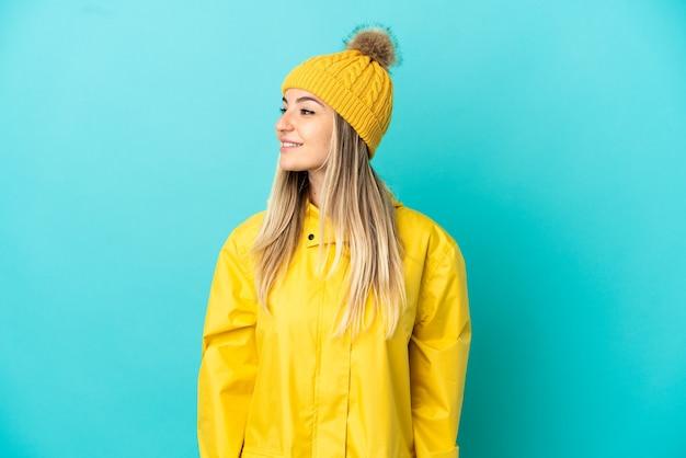 Jonge vrouw die een regendichte jas draagt over een geïsoleerde blauwe achtergrond die naar de zijkant kijkt