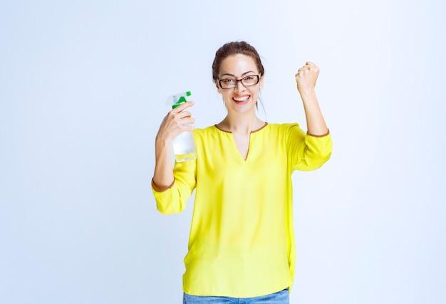 Jonge vrouw die een reinigingsspray vasthoudt en een teken van plezier toont