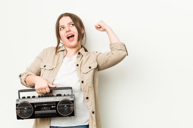 Jonge vrouw die een retro radio houdt die vuist na een overwinning opheft