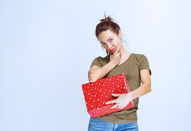 Jonge vrouw die een rode geschenkdoos vasthoudt en een goed idee heeft