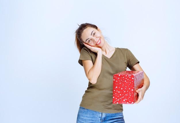 Jonge vrouw die een rode geschenkdoos vasthoudt en er erg van geniet