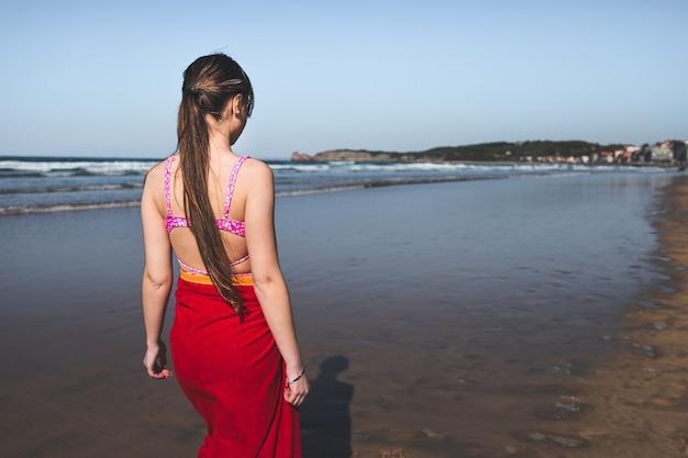Jonge vrouw die een rode handdoek en een roze bikini draagt die bij de waterrand op het strand loopt