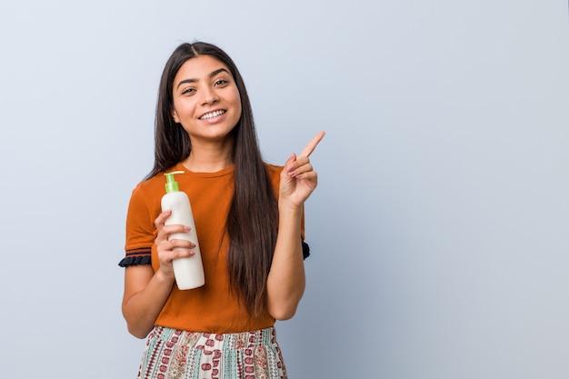 Jonge vrouw die een roomfles houdt glimlachend vrolijk richtend met weg wijsvinger
