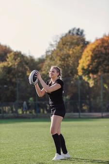 Jonge vrouw die een rugbybal houdt