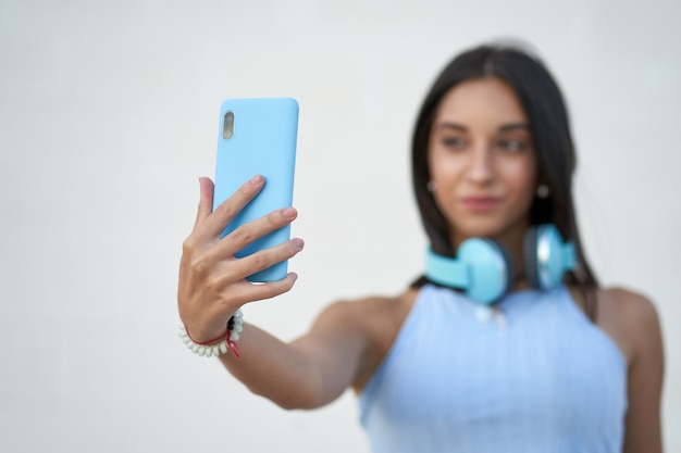 Jonge vrouw die een selfie maakt met de smartphone met een koptelefoon op haar nek geselecteerde focus