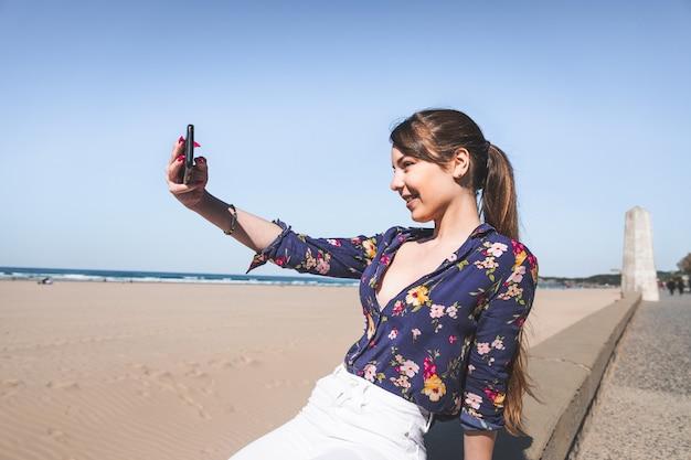 Jonge vrouw die een selfie maakt met een mobiele telefoon aan de strandzijde