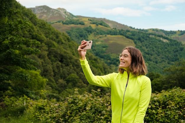 Jonge vrouw die een selfie maakt met haar mobiele telefoon na een wandeling in asturië