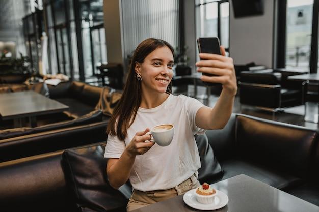 Jonge vrouw die een selfie neemt bij de coffeeshop