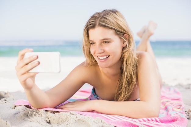 Jonge vrouw die een selfie op mobiele telefoon neemt