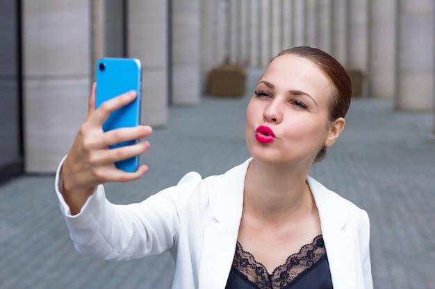 Jonge vrouw die een selfie op smartphone neemt.